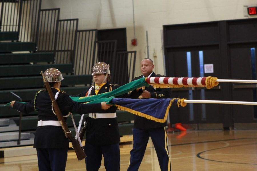 Uncasing the U.S. and Nebraska flags at the Dec. 4 JROTC annual inspection, sophomore Dominik Torres and junior Mia Edwards perform their color guard duties for Director of Army Instruction Michael DeBolt.