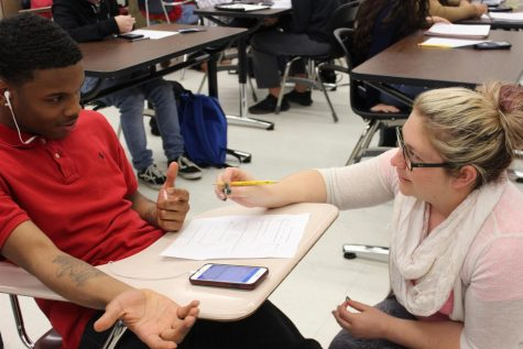 As a co-teacher for math teacher Allen Nesbitt's Geometry 2 class, special education teacher Rachel Allen helps junior Perry Jackson with his test.