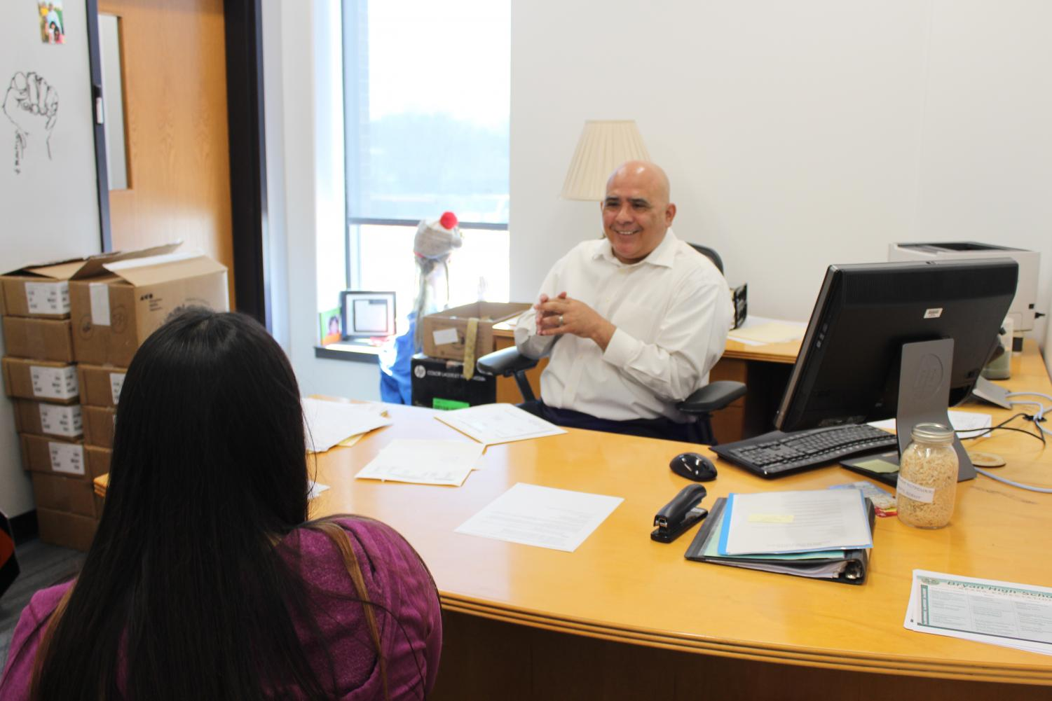 Working with a student, principal Robert Aranda gives her resources to help her with a situation she's going through.