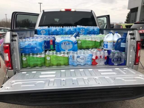In an additional vehicle, junior Taylor Richman loads up cases of water to be donated to flood victims.