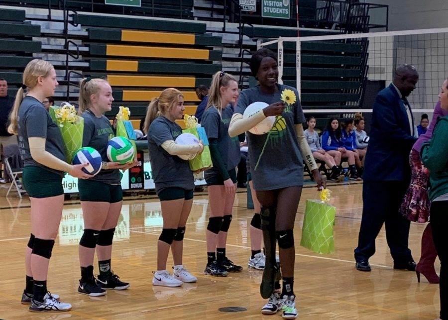 Walking+across+the+volleyball+court%2C+senior+Nyajuol+Lew+waves+to+her+varsity+teammates.+Lew+has+been+on+the+team+for+two+years.