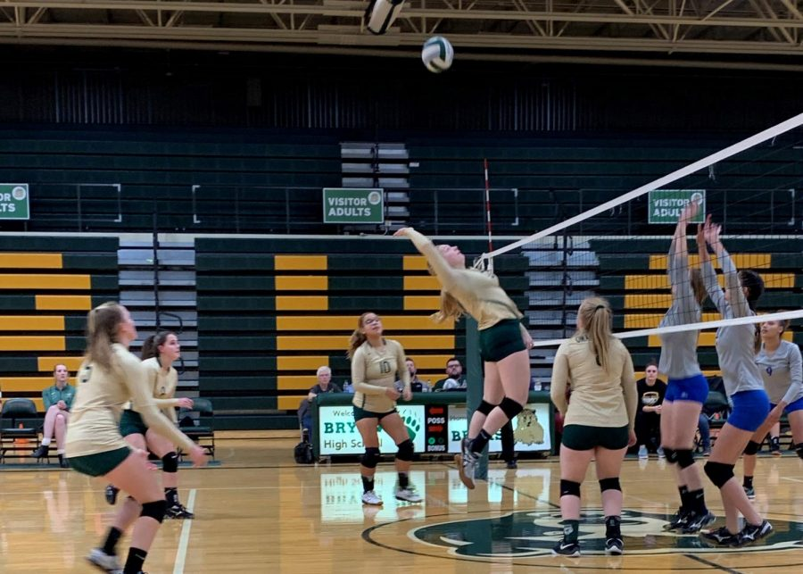 Attempting to hit the ball, junior Kaitlyn Schwenn jumps up and attacks. Although she missed the ball, Schwenn went on to have multiple blocks and kills in the game.