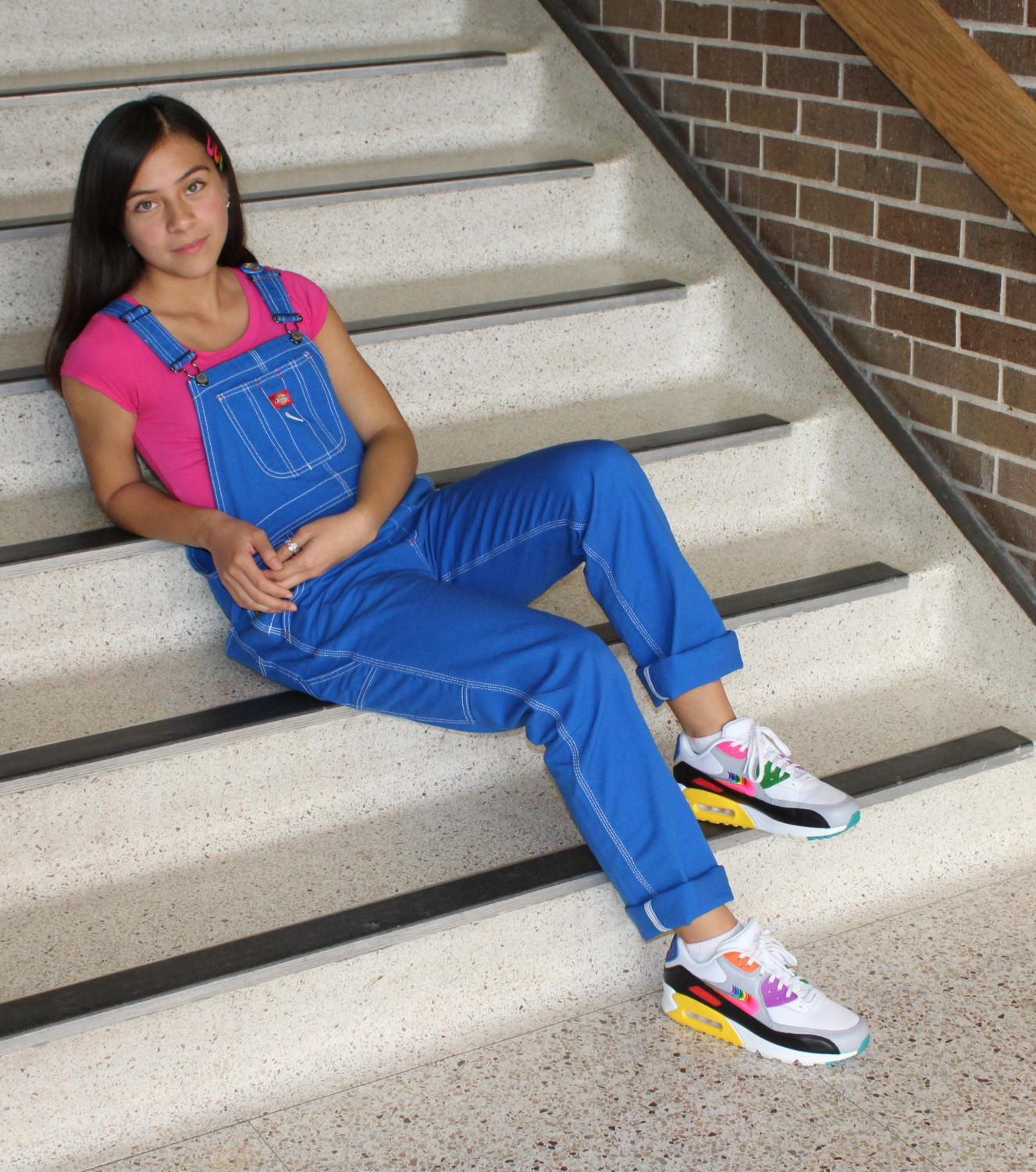 Relaxing on the stairs, Ruby Bugarin Arce looks up with confidence in her outfit. At home she decided to get the shoes because of all the colors on them, knowing that they would look good with a lot of her outfits.