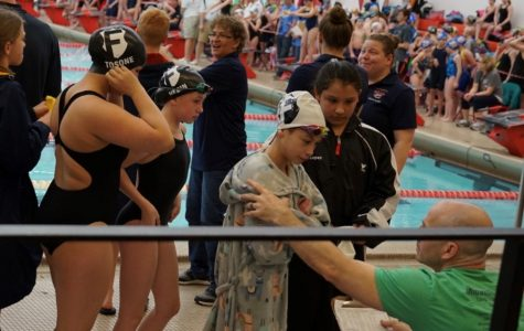 At a local swim meet, Drew Butler, new Bryan head coach and founder of the Omaha Swim Federation, goes over meet events with his athletes.