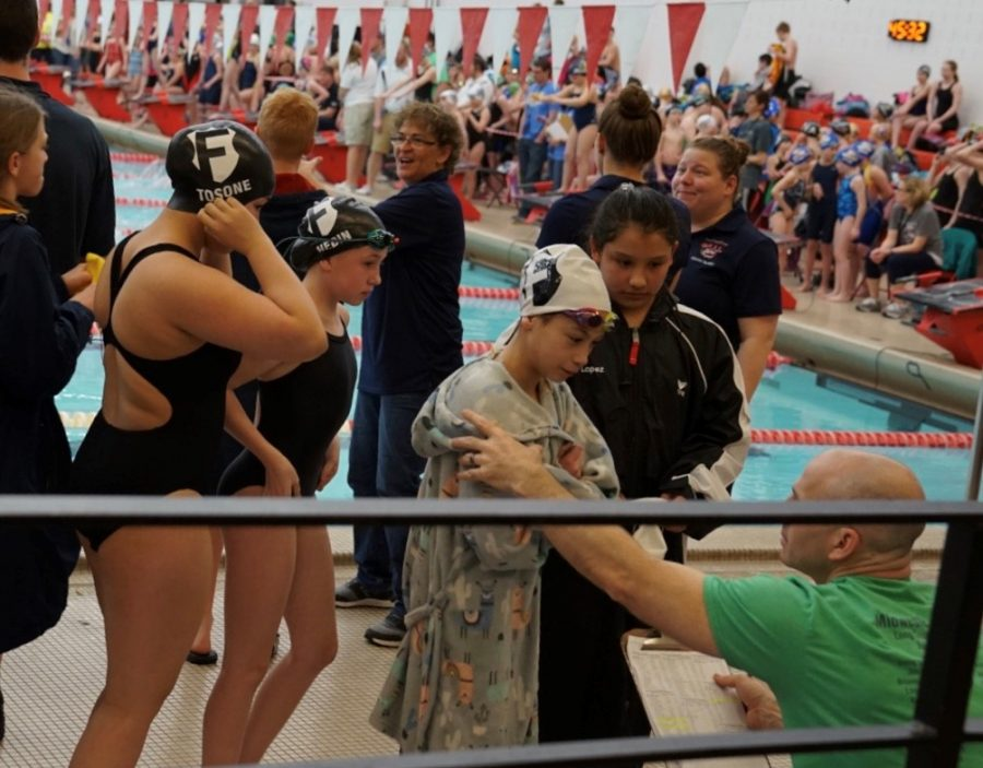 At+a+local+swim+meet%2C+Drew+Butler%2C+new+Bryan+head+coach+and+founder+of+the+Omaha+Swim+Federation%2C+goes+over+meet+events+with+his+athletes.