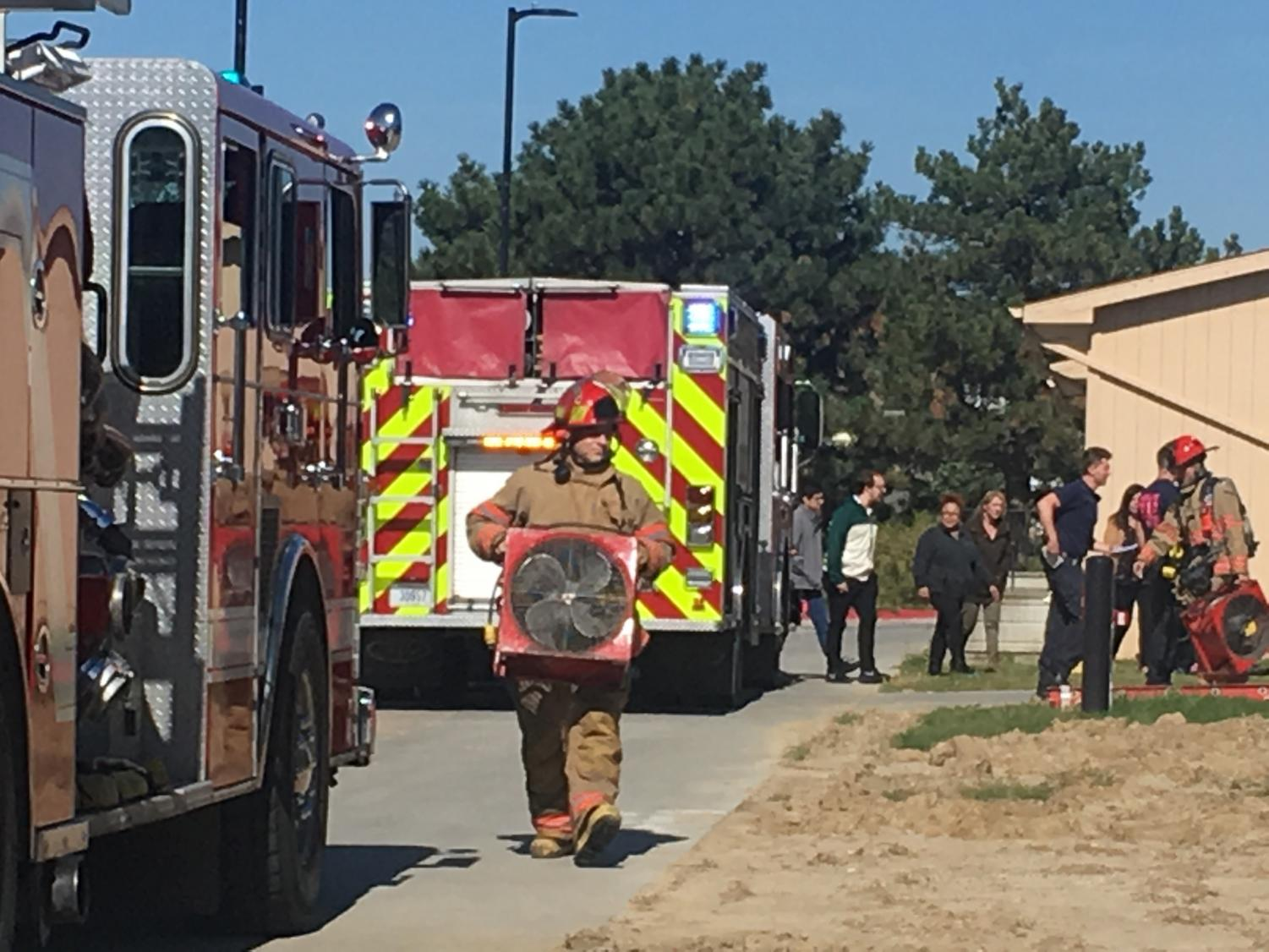 Bringing in fans, firefighters prepare to air out the burning plastic smell in the school caused by the cell phone that ignited.