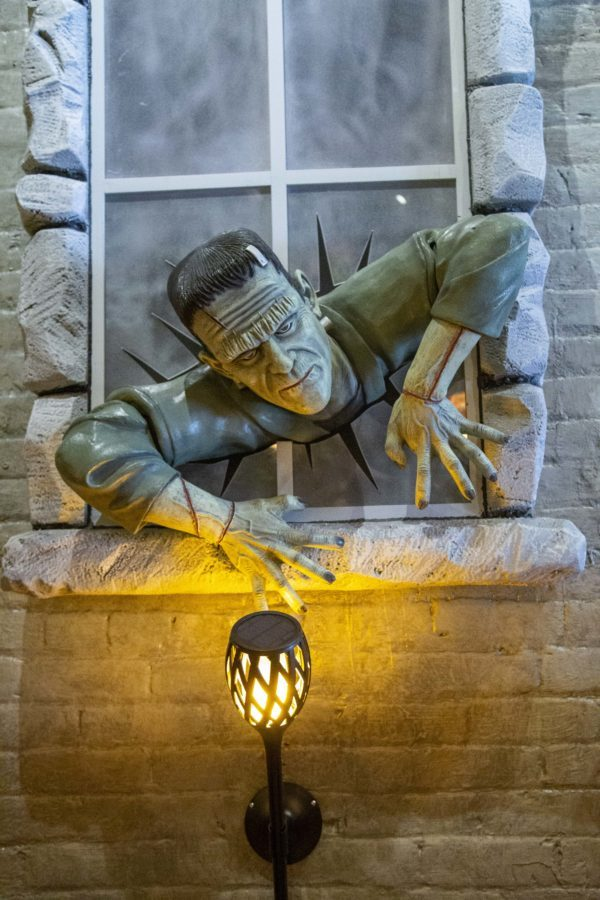 Breaking through the fake window on the wall of The Monster Club, Frankenstein and many other feature characters add to the Halloween decorations of the restaurant.