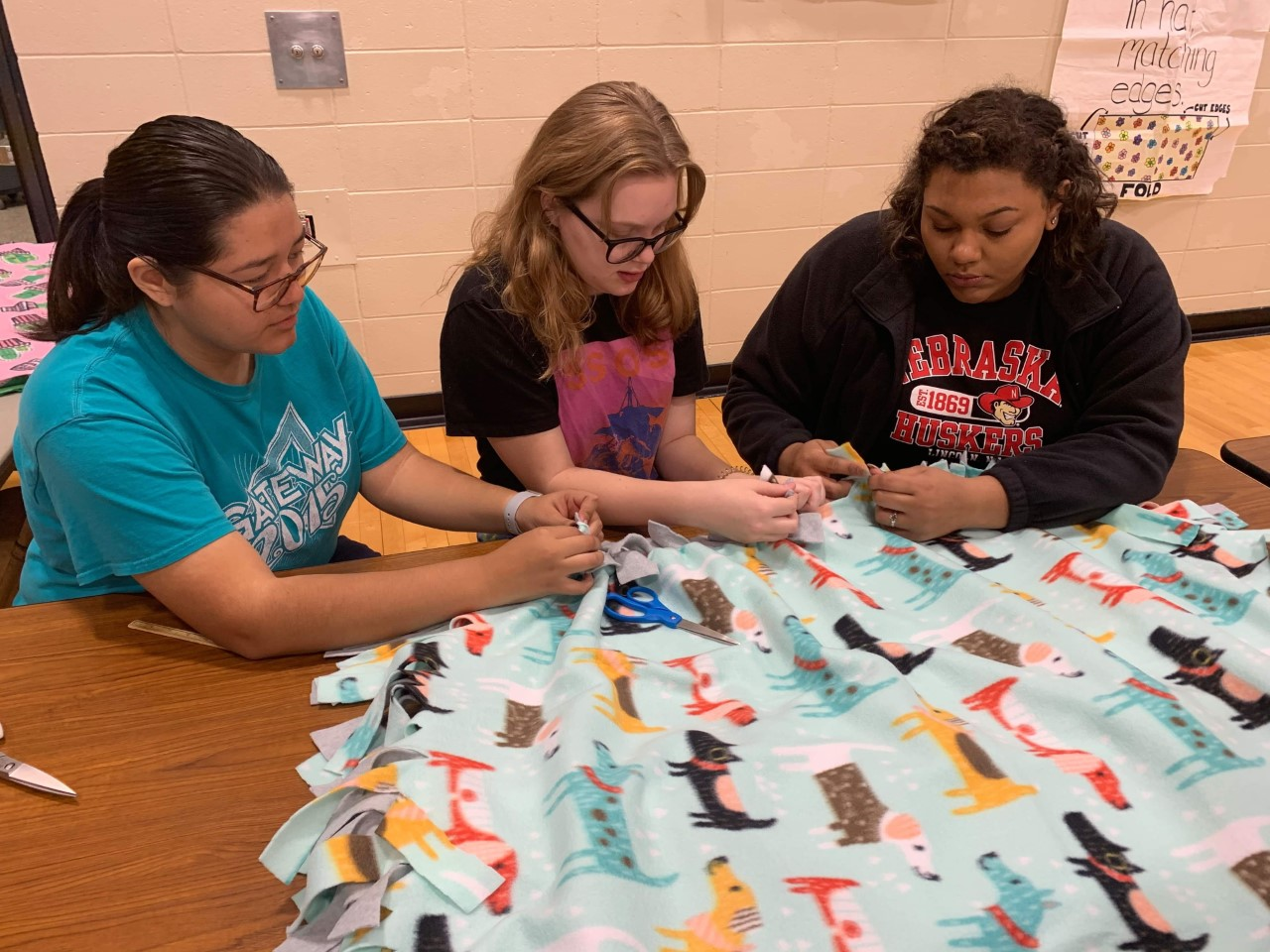 NHS members help tie the fleeces for the blankets. At the bi-annual Project Linus this year, students and past alumni helped make over 900 blankets that are going to be donated to different organizations for people in need.