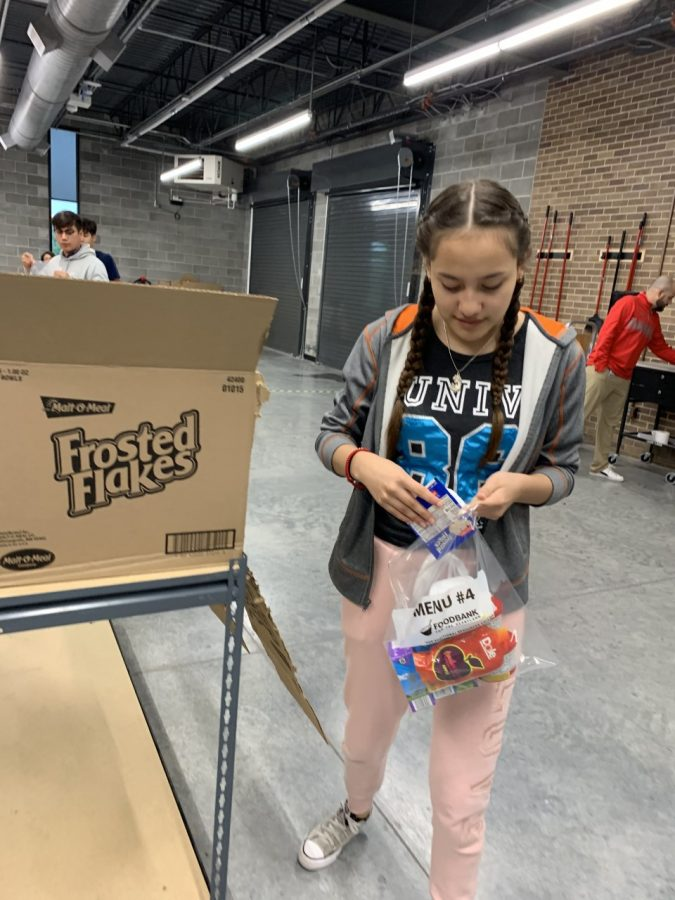 Putting Frosted Flakes in a bag, sophomore Jazmin Corona Jimenez finishes a weekend food package for the Food Bank for the Heartland's Backpack Program in her A1 TDL class. After packing each bag of food, Corona Jimenez put them in a box and when the box was full it went down the assembly line to be taped shut, labeled and prepared for shipment.