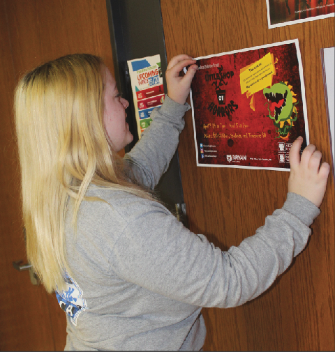 "Hanging up a poster on the auditorium doors for the upcoming musical, ""Little Shop of Horrors,"" senior Taylor Richman advertises the production."