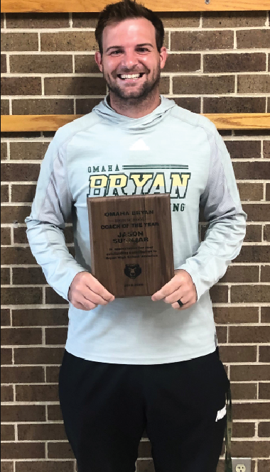 After being awarded Coach of the Year, head wrestling coach Jason Susnjar poses with his plaque for a photograph outside the gym in August.